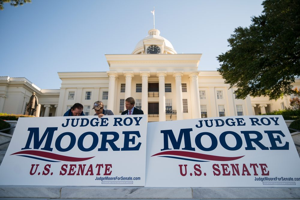 """Campaign staff members set up signs before the start of a 'Women For Moore"""" rally in support of Republican candidate for U.S. Senate Roy Moore, in front of the Alabama State Capitol, Nov. 17, 2017 in Montgomery, Ala. (Drew Angerer/Getty Images)"""