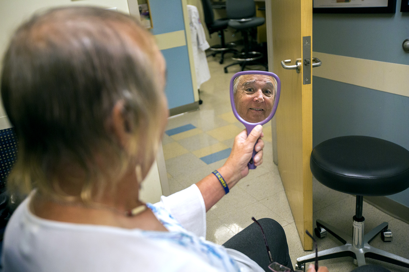 Tami Goodhue looks in a mirror during her appointment to review information about the facial feminization surgery she wishes to have done at Boston Medical Center. (Jesse Costa/WBUR)