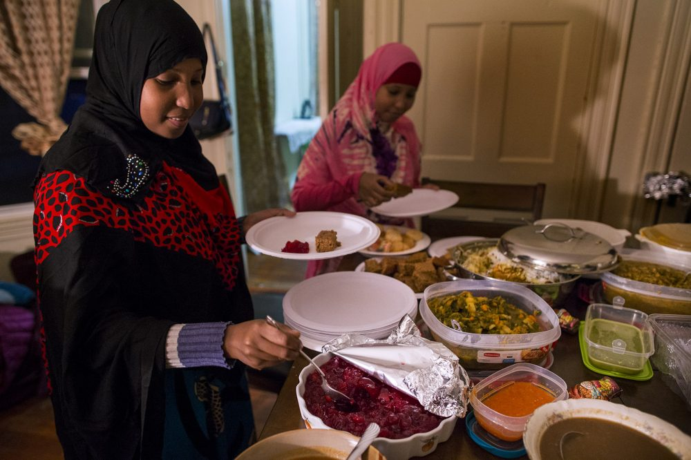Hawo Ahmed helps herself to cranberry sauce as twin sister Muna picks up a piece of gingerbread during a Thanksgiving feast celebrated on Sunday with volunteers from the International Institute of New England. (Jesse Costa/WBUR)