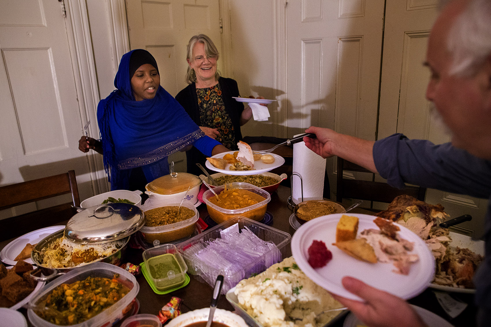 Dan Chernoff serves Asha Ahmed her very first slice of Thanksgiving turkey. Refugees from Somalia, this is the Ahmed family's first Thanksgiving in the United States. (Jesse Costa/WBUR)