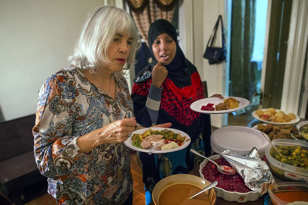 A curious Janet Amphlett listens as Hawo describes the different Somali dishes that are offered on the table. (Jesse Costa/WBUR)
