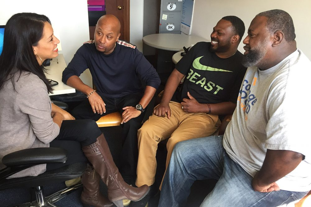 Trinity counselor Blanca Valentin, left, counsels College Bound Dorchester advisers Warren Williams, second from left, I.V. Johnson, second from right, and Will Dunn, right, who work with youths with gang ties at College Bound Dorchester's headquarters. (Fred Thys/WBUR)