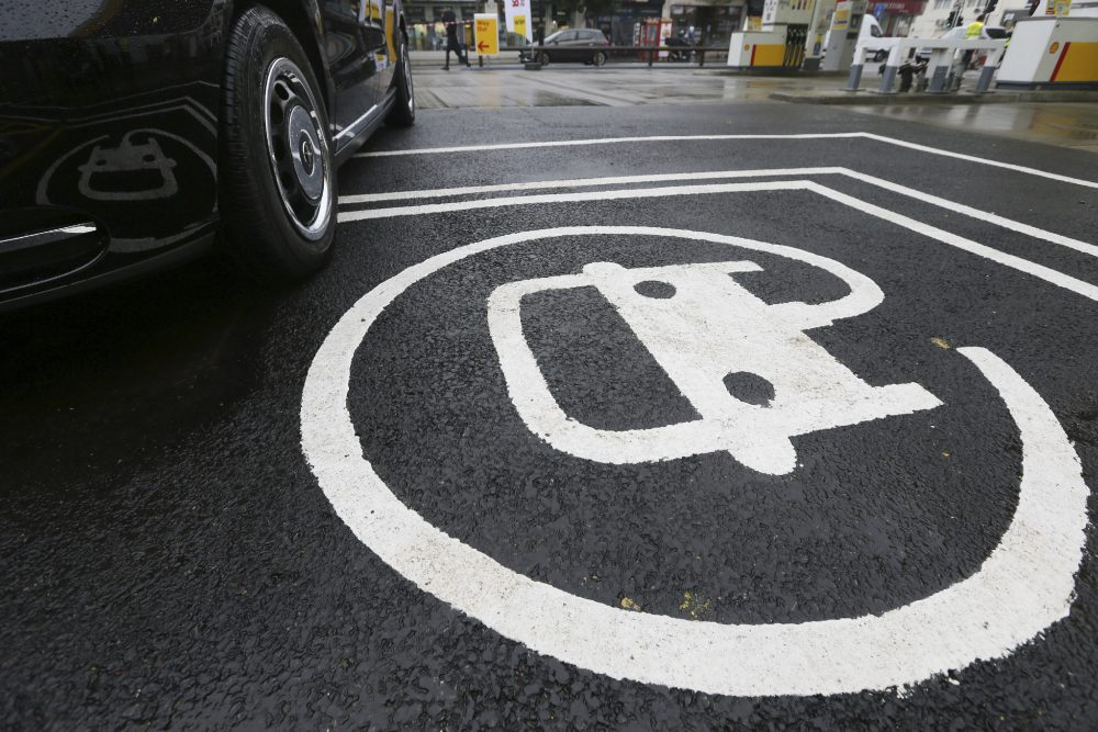 The electric vehicle recharging sign, as a new TX Cab London taxi is parked at a charging station during a media opportunity at a Shell petrol station in London on Oct. 18. (Tim Ireland/AP)