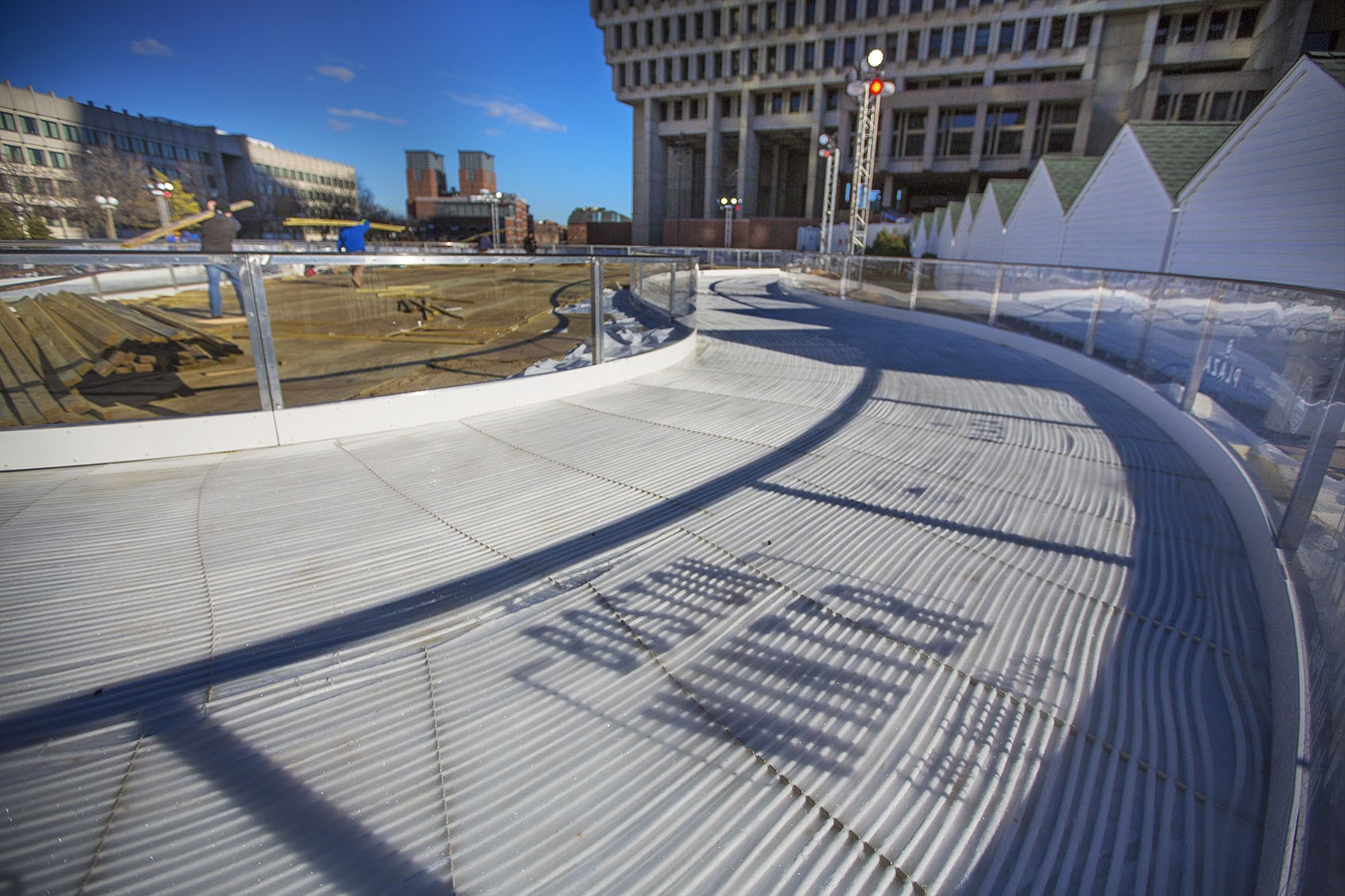"""Workers finish putting together the skating rink for """"Boston Winter"""" at City Hall Plaza last year. (Jesse Costa/WBUR)"""