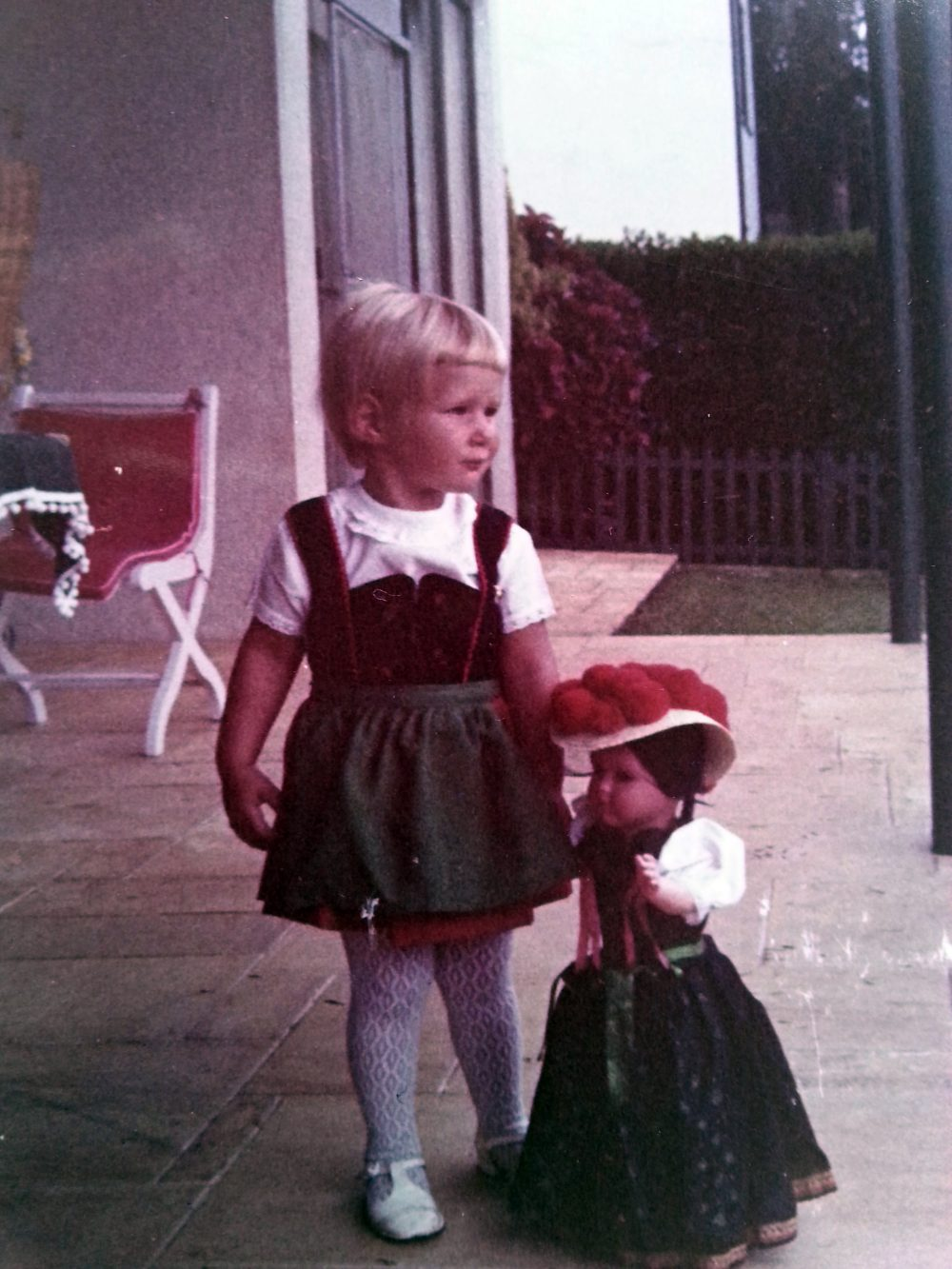 Julie, aged 3, in Brazil, dragging along a Bavarian doll and dressed in the dirndl, a traditional German dress, which she wore when her grandparents came to visit. (Courtesy of Julie Lindahl)