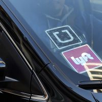 A driver displaying Lyft and Uber stickers on his car (Richard Vogel/AP)
