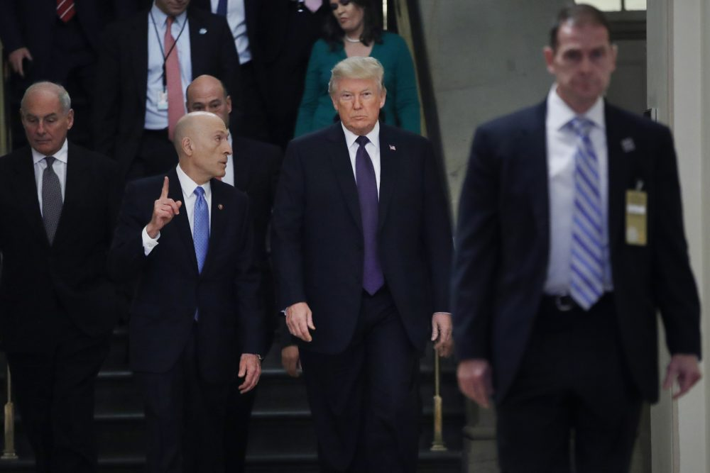 President Donald Trump, center, walks next to Paul Irving, left, the House Sergeant at Arms, Thursday, Nov. 16, 2017, on Capitol Hill in Washington. Trump is at the Capitol for a pep rally with House Republicans, shortly before the chamber is expected to approve the tax bill over solid Democratic opposition. At far left is White House Chief of Staff John Kelly. (Jacquelyn Martin/AP)