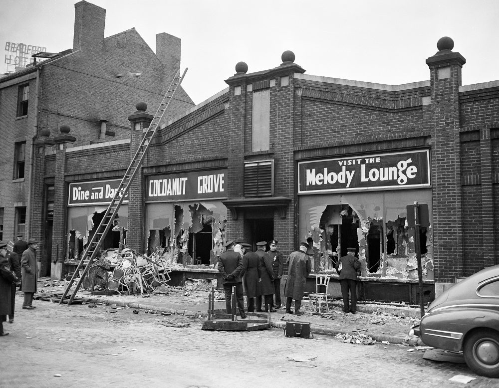 """Boston police and firemen watch rear entrance to the """"Melody Lounge"""" section of the Cocoanut Grove Night Club, Nov. 29, 1942. Debris from broken chairs, table and personal effects of some guests of the club when the fire broke out last night litter sidewalk and gutter. Over 400 people perished.  (AP Photo)"""