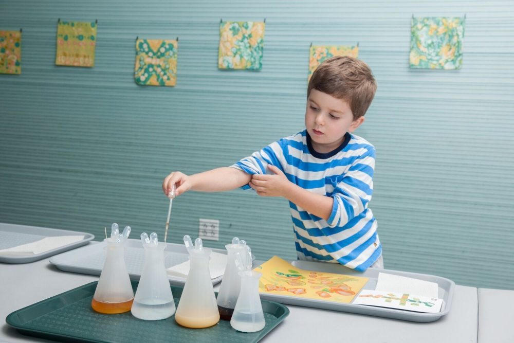 A museum visitor experiments with various liquids, including Boston Harbor water. (Courtesy Galya Feierman/ICA)