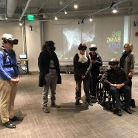 """MIT Museum visitors use virtual-reality gear to experience """"The Enemy,"""" Karim Ben Khelifa's exploration of conflict zones and the people who inhabit them. (Courtesy MIT Museum)"""