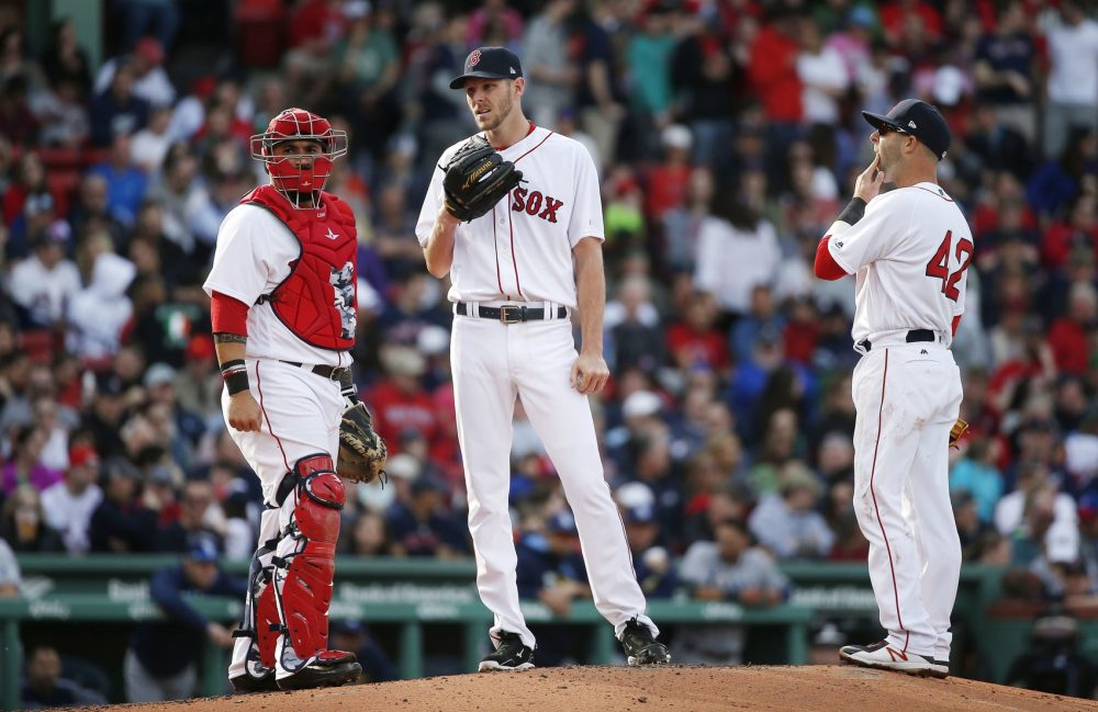 Boston Red Sox's Chris Sale, center, waits on the mound for a visit from pitching coach Carl Willis with Sandy Leon, left, and Dustin Pedroia during the third inning of a baseball game against the Tampa Bay Rays in Boston, Saturday, April 15, 2017, in Boston. (AP Photo/Michael Dwyer)