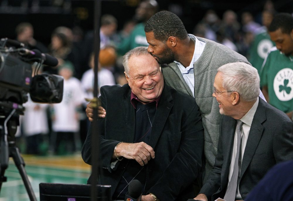 As Celtics braodcaster Tommy Heinsohn (left) and his partner Mike Gorman (right) were sitting courtside doing their pre game piece, former Celtics forward Walter McCarty (center) walked by and planted a kiss on the smiling Heinsohn's forehead. The Boston Celtics hosted the Washington Wizards in a regular season NBA game at the TD Garden in 2012. (Jim Davis/Globe Staff)
