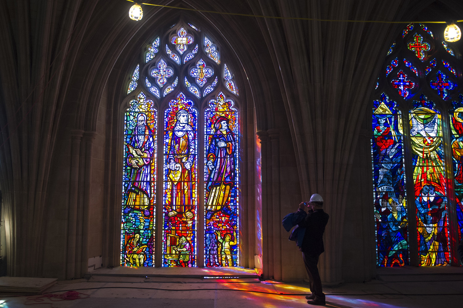 A reporter takes a photograph of a stained glass window at the Washington National Cathedral. (Cliff Owen/AP)