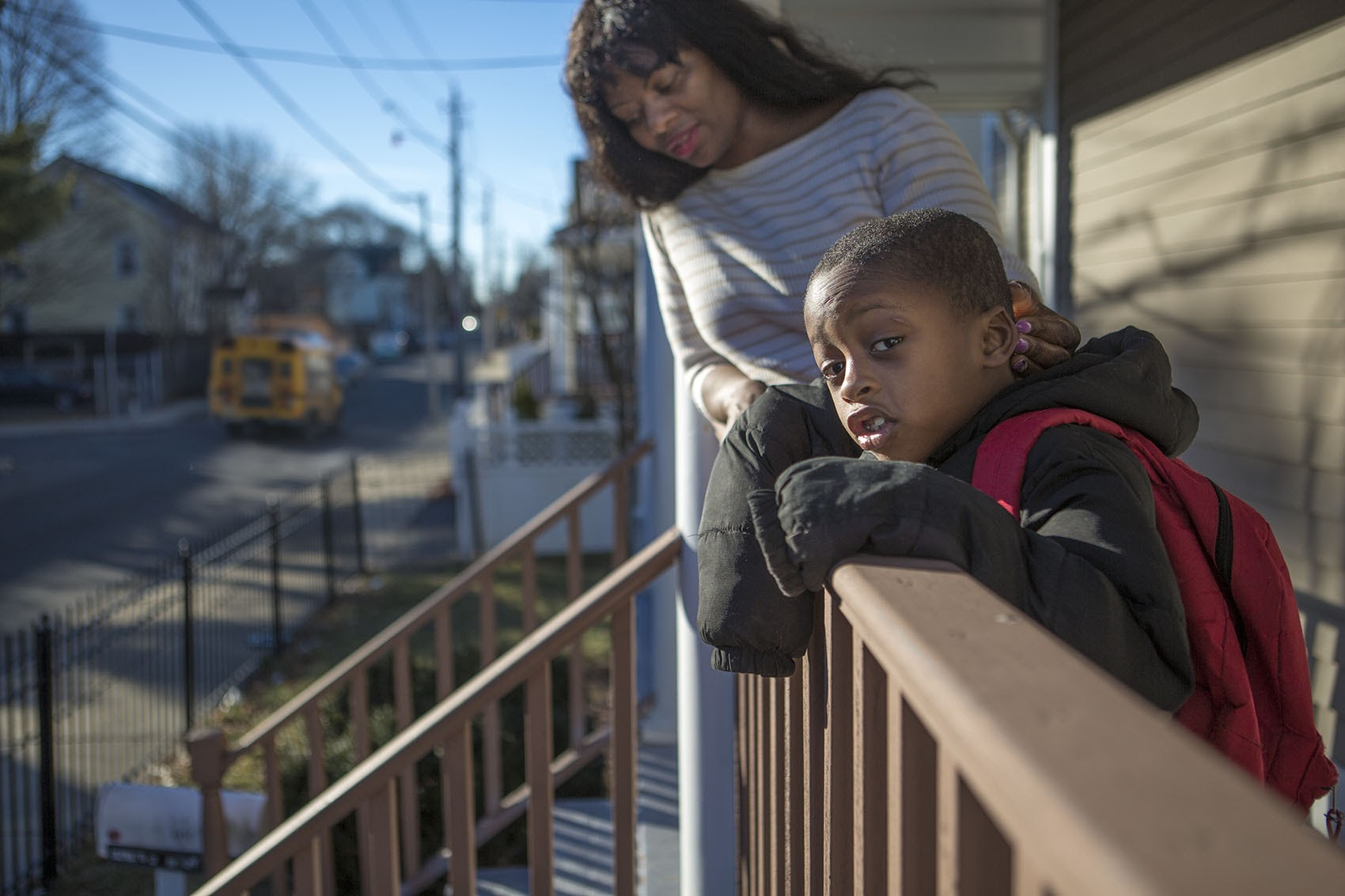 On the front porch, a 5-year-old student from Dorchester watches for his school bus with his mother in 2016. (Jesse Costa/WBUR)