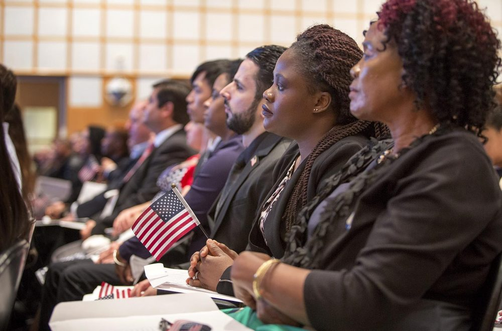 Marie Claire Kum, from Cameroon, holds a U.S. flag as she listens intently at the naturalization ceremony at the JFK Museum in Boston. (Robin Lubbock/WBUR)