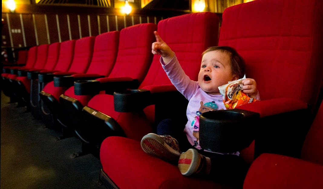 "Eighteen-month-old Laura points at the screen of the Coolidge Corner Theatre before a screening of ""Faces Places."" (Robin Lubbock/WBUR)"