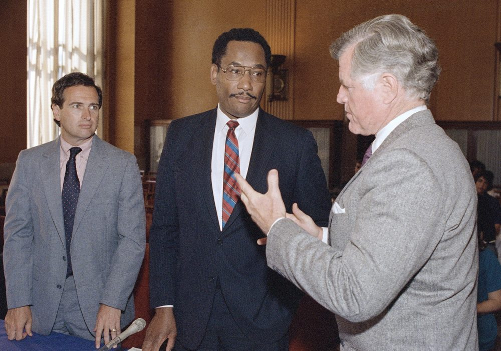 Sen. Edward M. Kennedy, D-Mass., speaks with district attorney Kevin M. Burke, left, of Essex County, Mass., and Houston Chief of police Lee Brown, center, during a hearing on drug enforcement before the Senate Judiciary Committee Tuesday, June 14, 1988 in Washington. (John Duricka/AP)