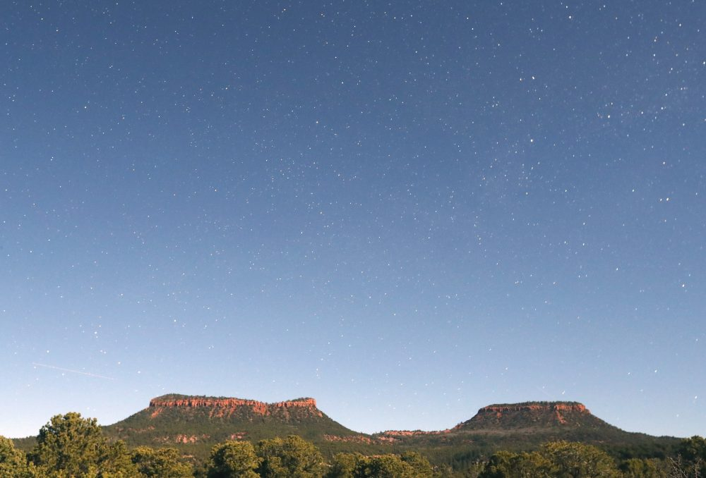 """This time-exposed photo taken at midnight shows the stars and the two bluffs known as the """"Bears Ears"""" in the Bears Ears National Monument on May 12, 2017, outside Blanding, Utah. (George Frey/Getty Images)"""