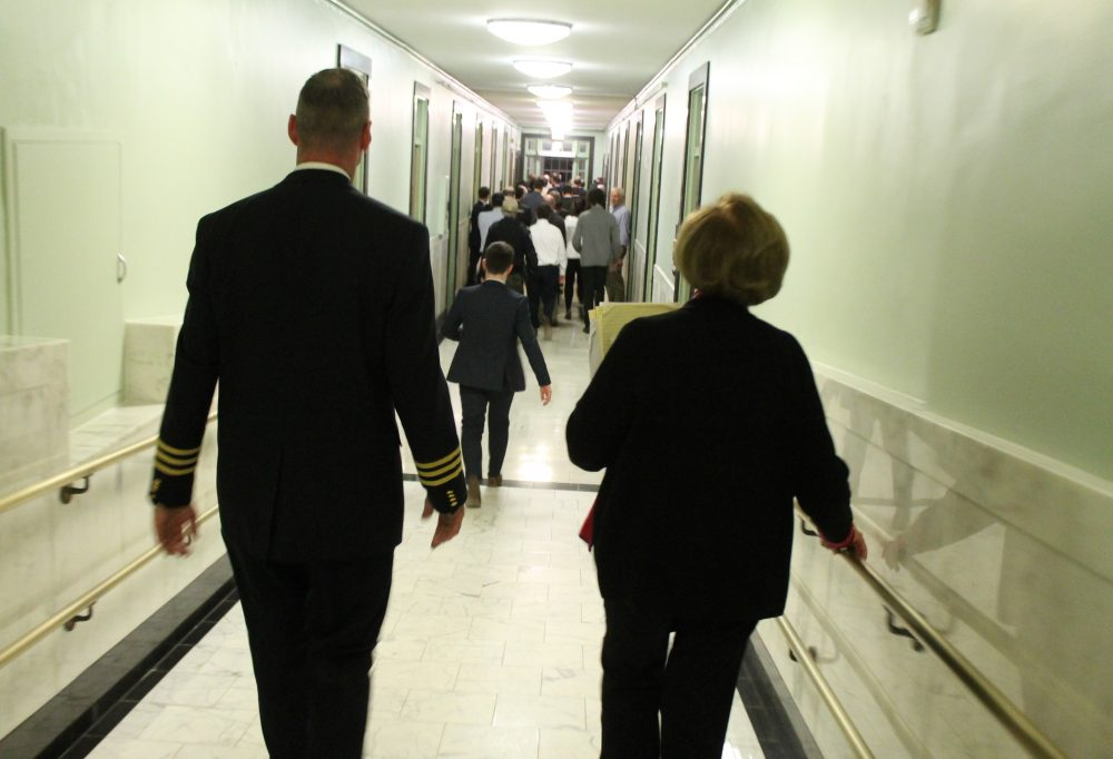 Chief Court Officer Paul Dooley walked Majority Leader Harriette Chandler toward the Gardner Auditorium where her colleagues elected her acting Senate president. (Sam Doran/SHNS)