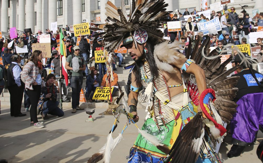 A supporter of the Bears Ears and Grand Staircase-Escalante National Monuments dances with a headdress during a rally Saturday, Dec. 2, 2017, in Salt Lake City. (Rick Bowmer/AP)