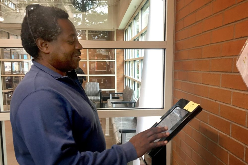Pine Street Inn resident John Alex Codio prepares to send a message to an old friend using an iPad set up by Miracle Messages. Codio was the first to use the device after it was installed in October. (Simón Rios/WBUR)