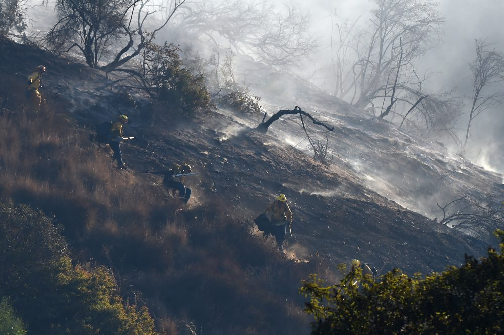 A fire team hand crew descends a steep slope to prevent fire from jumping to the west side of Interstate 405 near the Bel Air area of Los Angeles, Dec. 6, 2017. (Robyn Beck/AFP/Getty Images)