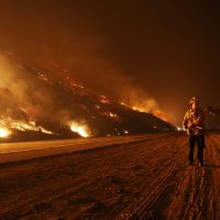 Firefighters monitor a section of the Thomas Fire along the 101 freeway on Dec. 7, 2017 north of Ventura, Calif. Strong Santa Ana winds are rapidly pushing multiple wildfires across the region, expanding across tens of thousands of acres and destroying hundreds of homes and structures.  (Mario Tama/Getty Images)