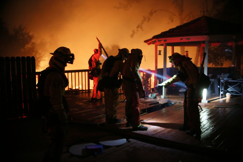 Firefighters work to save a home from an encroaching fire during the Lilac Fire in Bonsall, Calif., on Thursday, Dec. 7, 2017. (Sandy Huffaker/AFP/Getty Images)