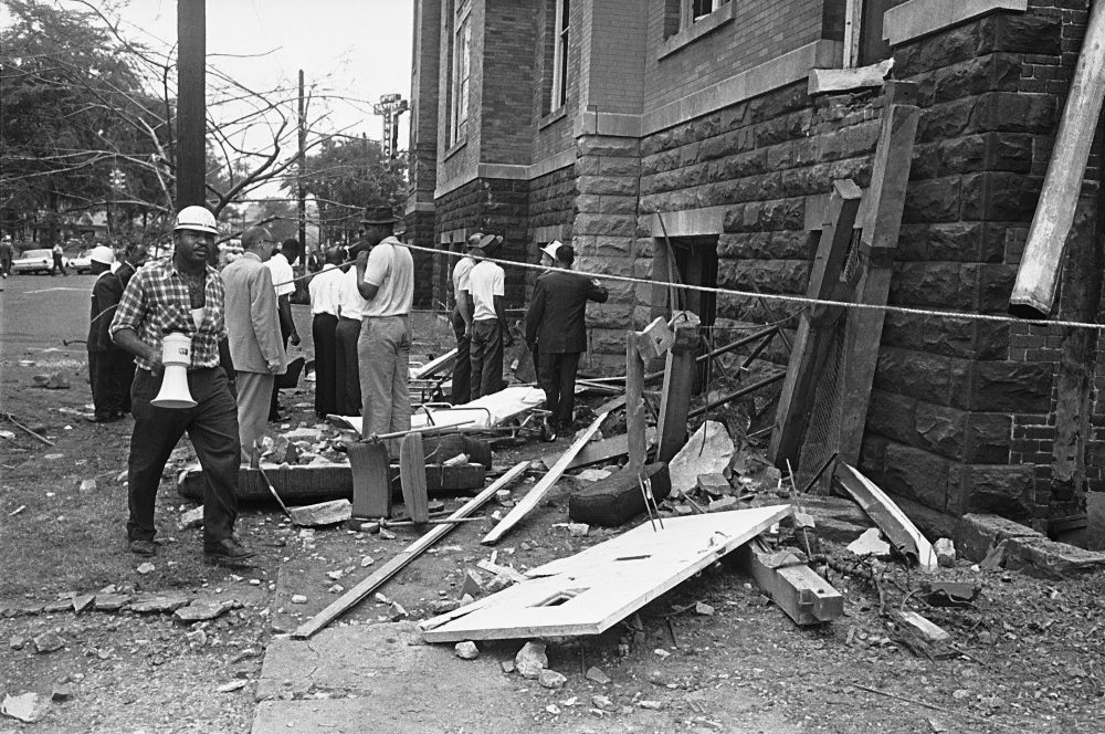 A civil defense worker and firemen walk through debris from an expolsion which struck the 16th street Baptist Church, killing and injuring several people, in Birmingham, Ala. on Sept. 15, 1963. (AP Photo)