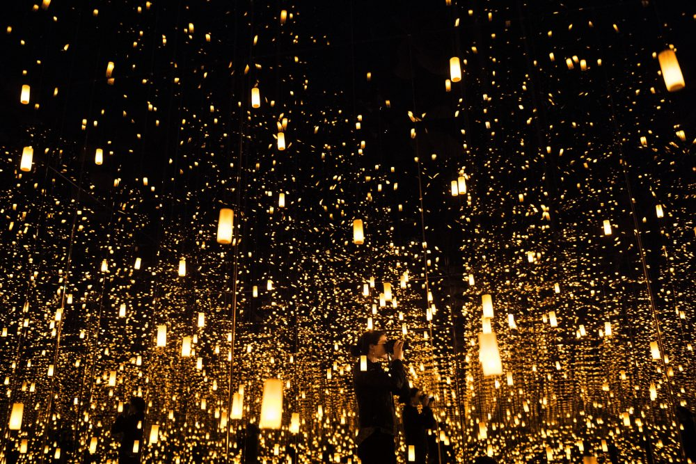 """A woman photographs inside the """"Aftermath of Obliteration of Eternity"""" room during a preview of the Yayoi Kusama's """"Infinity Mirrors"""" exhibit at the Hirshhorn Museum on Feb. 21, 2017 in Washington, D.C. (Brendan Smialowski/AFP/Getty Images)"""