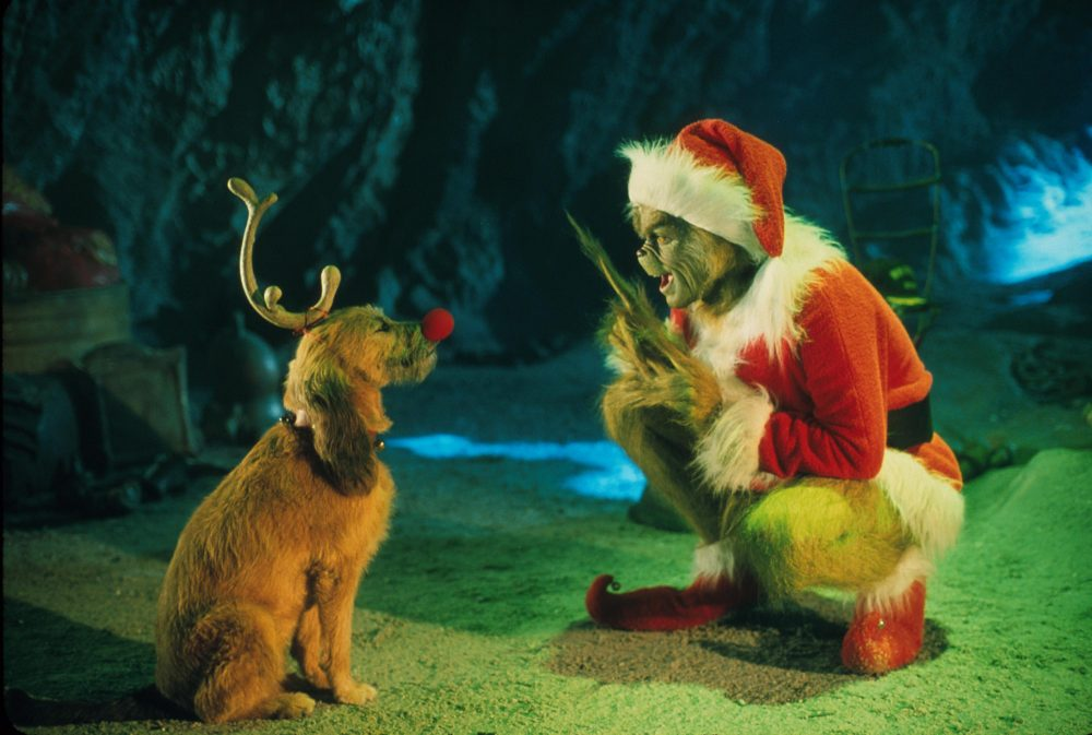 "The Grinch, played by Jim Carrey, conspires with his dog Max to deprive the Whos of their favorite holiday in the live-action adaptation ""Dr. Seuss' How The Grinch Stole Christmas."" (Getty Images)"