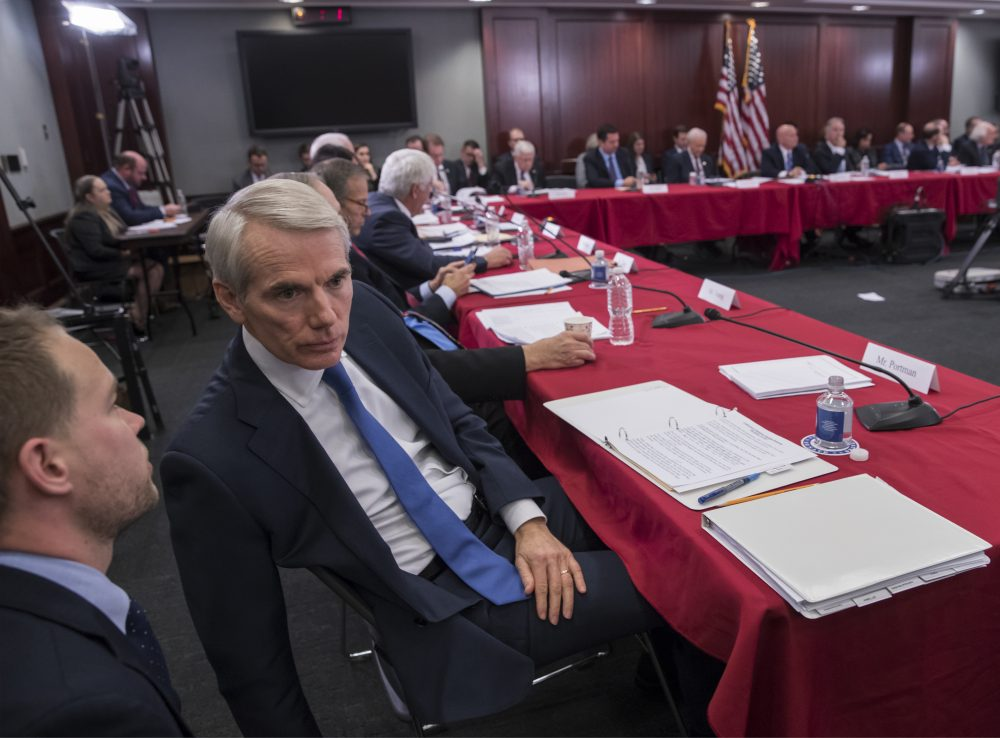 Sen. Rob Portman, R-Ohio, a member of the tax-writing Senate Finance Committee, confers with an aide as tax bill conferees gather to work on the sweeping GOP plan, on Capitol Hill in Washington, Wednesday, Dec. 13, 2017. (J. Scott Applewhite/AP)