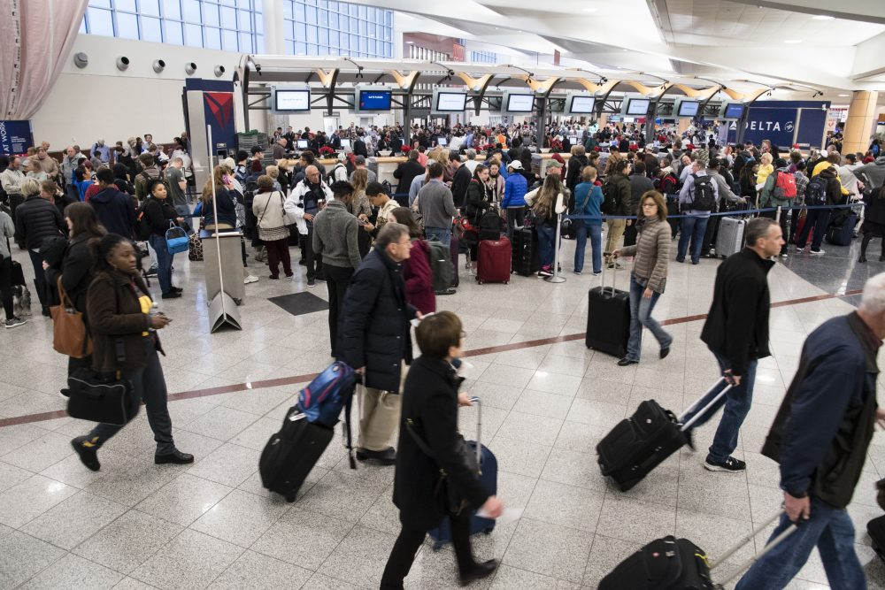 Passengers make their way past long lines at a ticket counter at Hartfield-Jackson Atlanta International Airport, Monday, Dec. 18, 2017, in Atlanta. Power has been restored at the airport after a Sunday blackout caused by a fire stranded thousands of passengers and grounded at least 1,500 flights. (John Amis/AP)