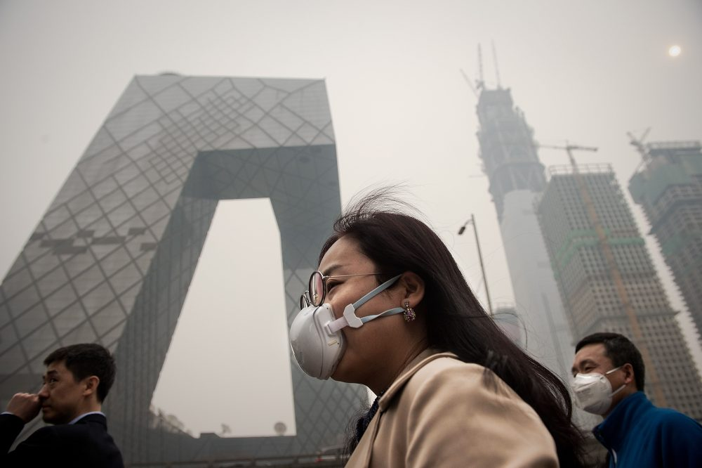 A woman wearing a protective pollution mask walks on a street in Beijing on March 20, 2017. (Nicolas Asfouri/AFP/Getty Images)