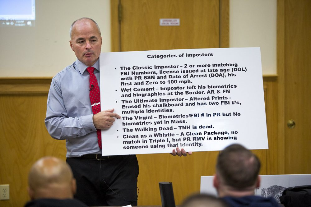 "Officer James Scott of the Saugus Police Department holds up a placard with the categories of so-called ""impostors"" during an impostor training class at Bristol County Jail and House of Correction in North Dartmouth. (Jesse Costa/WBUR)"
