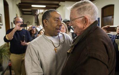 """Darrell Jones embraces Rev. William Barry, who he calls """"Dad,"""" following his release on bail after serving 32 years in prison for a murder he maintains he did not commit. (Jesse Costa/WBUR)"""