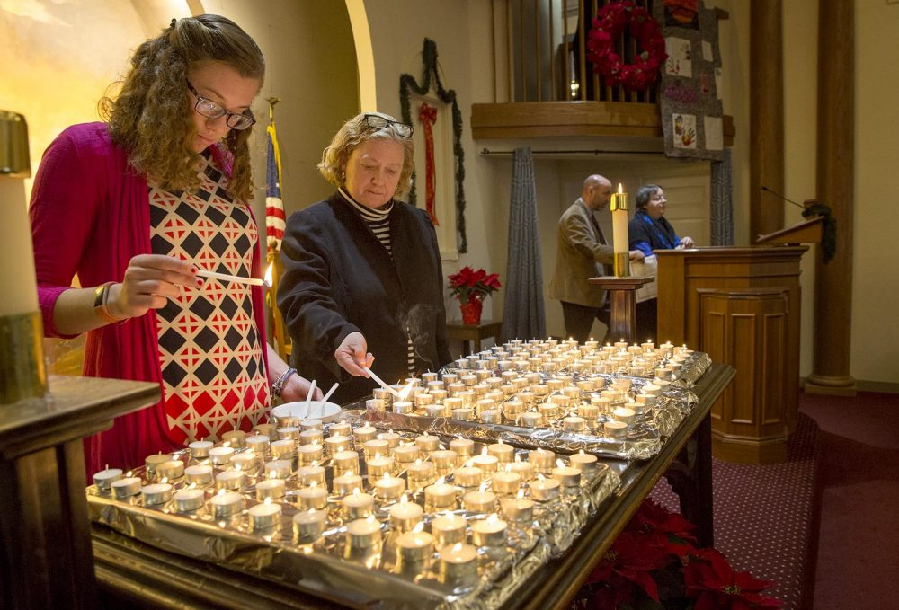 Elizabeth Hadley, left, and Lisa Barbin light candles at the 28th annual Interfaith Homeless Memorial Service to remember homeless people who died on the streets of Boston in 2017. (Robin Lubbock/WBUR)