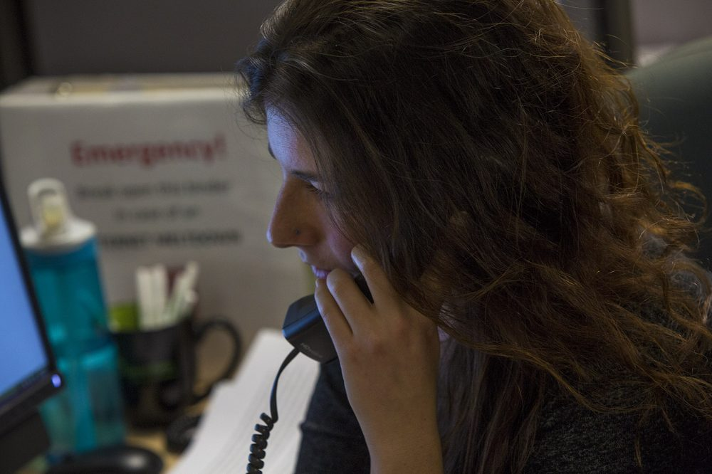 Samaritans volunteers typically answer calls and texts in a call center. They are currently working from home because of the pandemic. Here, a Samaritans volunteer, Emma, is pictured speaking with a caller in 2017. (Jesse Costa/WBUR)
