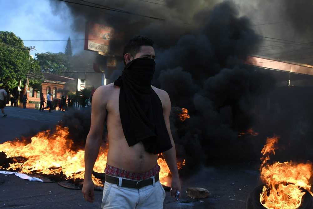 Supporters of the presidential candidate for the Opposition Alliance Against the Dictatorship, Salvador Nasralla, set fire to tires as they protest against the re-election of President Juan Orlando Hernandez in elections marred by suspicions of fraud, outside the U.S. Embassy in Tegucigalpa on Dec. 21, 2017. (Orlando Sierra/AFP/Getty Images)