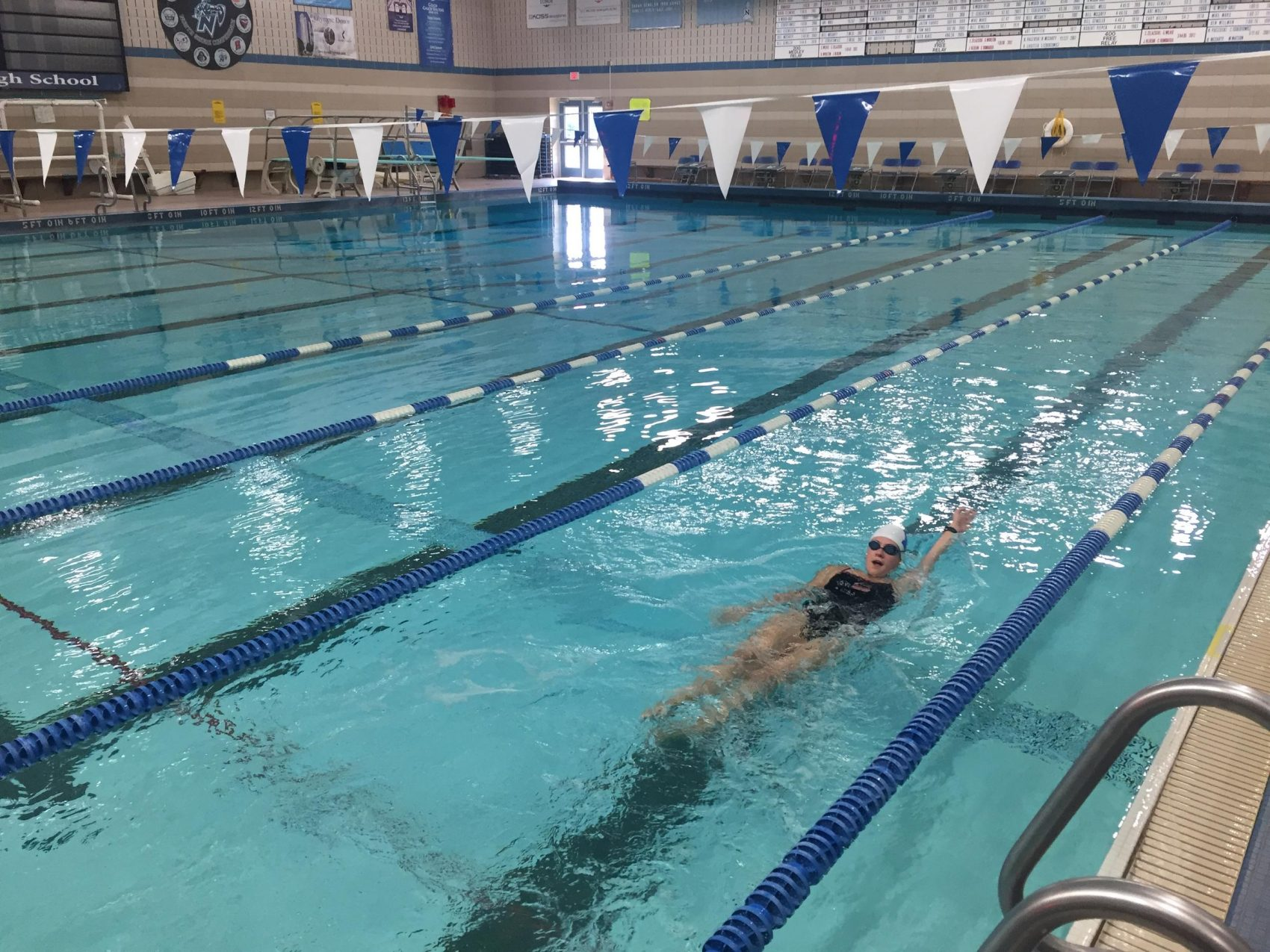 Nicolet High School senior Elizabeth Sullivan demonstrates how she counts strokes for her races. (Rachel Morello/WUWM)