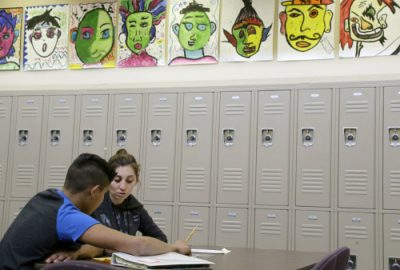ADVANCE FOR MONDAY, MAY 2, 2016 AND THEREAFTER - In this April 19, 2016 photo, Laurie Millan, a para-professional and tutor, works with a student during an after school tutoring session at San Francisco International High School, in San Francisco. While some districts in numerous states have discouraged migrant minors from Central America from enrolling in their schools, the school accommodated its youths by rewriting young-adult novels at a basic level to spark the newcomers' interest in reading.  (AP Photo/Jeff Chiu)