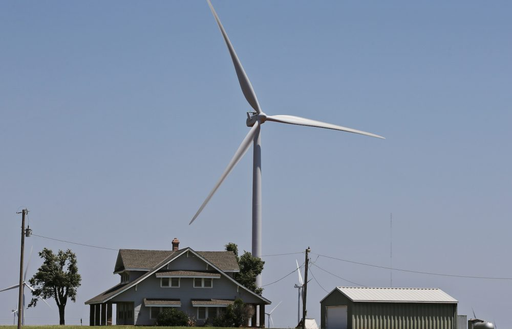 In this Monday, June 12, 2017 photo, a house is dwarfed by a near-by wind turbine near Okarche, Okla. (AP Photo/Sue Ogrocki)