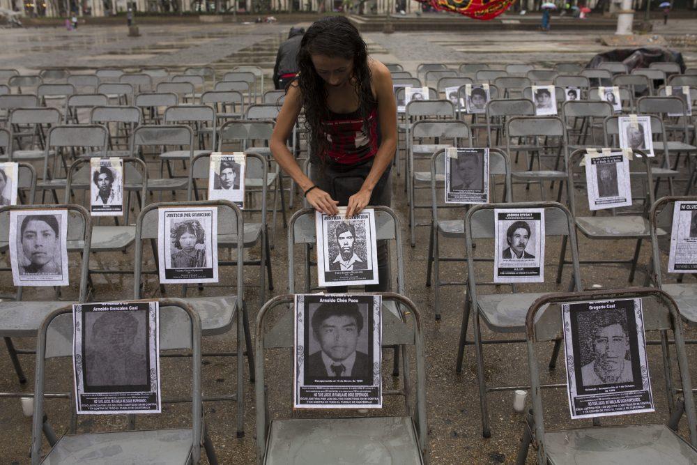 """María Meza Paniagua adjunta el retrato de un desaparecido a una silla, en una ceremonia que marca el Día Nacional Contra la Desaparición Forzada, en Guatemala, el 21 de junio de 2017. Según grupos de derechos humanos, más de 40,000 personas fueron """"desaparecidas"""" durante los 36 años del conflicto interno en Guatemala. (Moisés Castillo/AP)"""