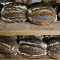 In this photo taken Friday, Aug. 11, 2017, are freshly baked loaves of bread on a rack at the Tartine Manufactory in San Francisco. For a bread lover, no destination is more alluring than San Francisco. (AP Photo/Eric Risberg)