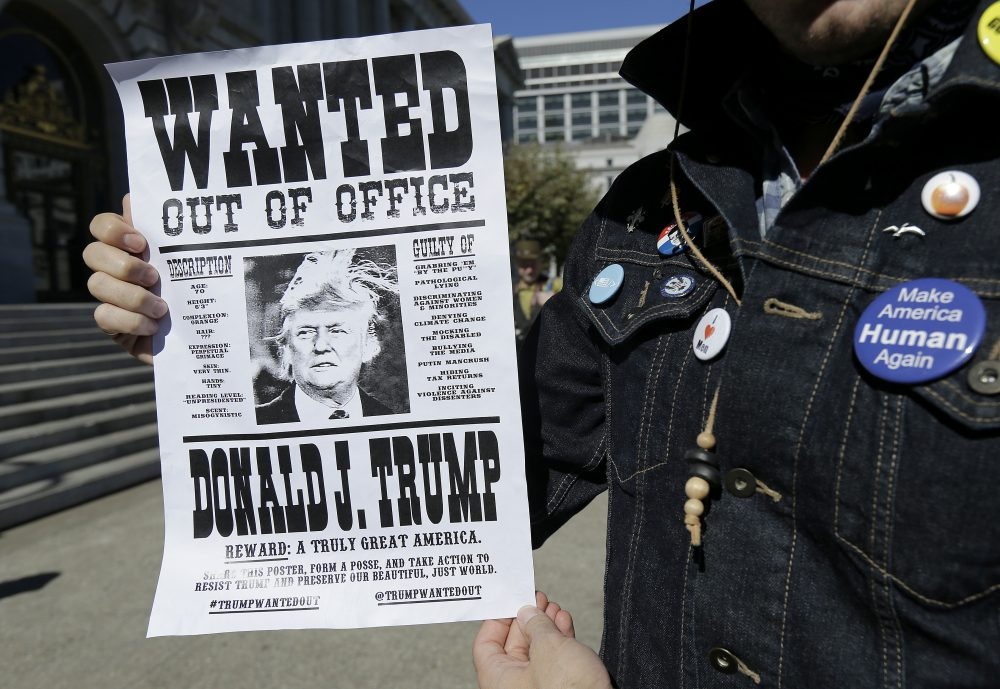 Andrew Fitch holds up a sign at a rally calling for the impeachment of President Donald Trump in San Francisco, Tuesday, Oct. 24, 2017. (Jeff Chiu/AP)