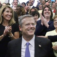 In this 2016 file photo, Gov. Charlie Baker smiles with Lt. Gov. Karen Polito, left, after he signed a bill into law at the State House in Boston. Baker and Polito both will seek a second term in the 2018 election. (Elise Amendola/AP)