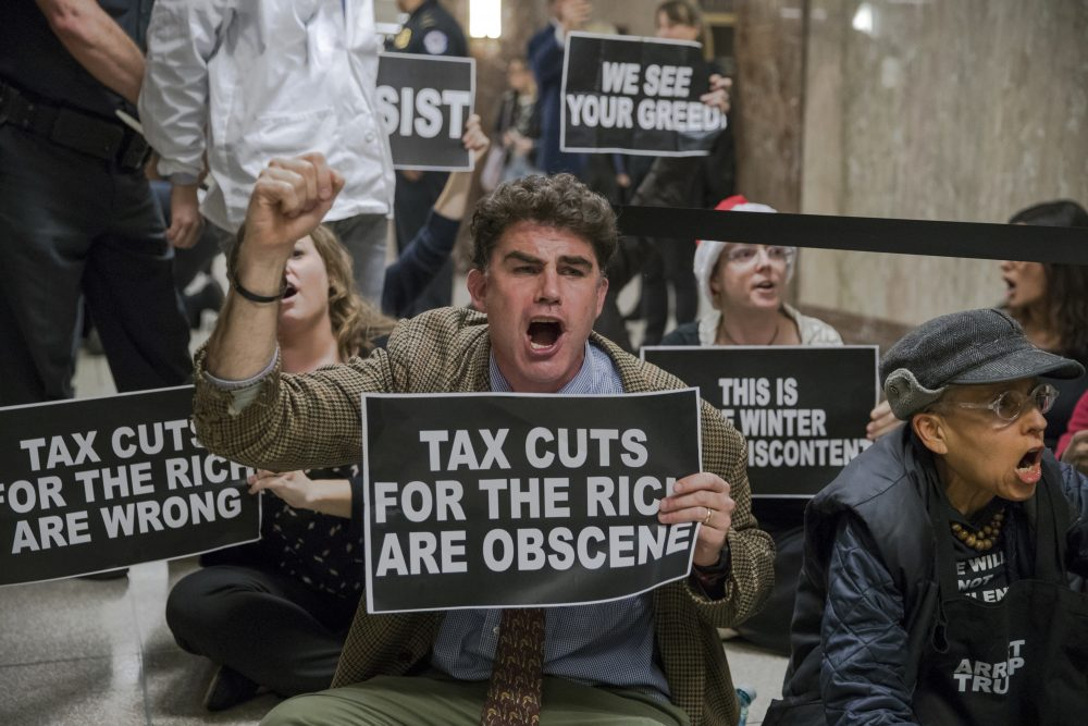 Protesters shout their disapproval of the Republican tax bill outside the Senate Budget Committee hearing room on Capitol Hill in Washington, Tuesday, Nov. 28, 2017. (J. Scott Applewhite/AP)