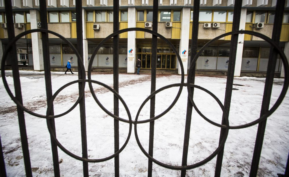 People walk at the building of the Russian Olympic Committee is seen through a gate decorated with the Olympic rings in Moscow, Russia, Wednesday, Dec. 6, 2017. The International Olympic Committee has barred the Russian team from competing in Pyeongchang in February over widespread doping at the last edition of the Winter Games in 2014. (Alexander Zemlianichenko/AP)