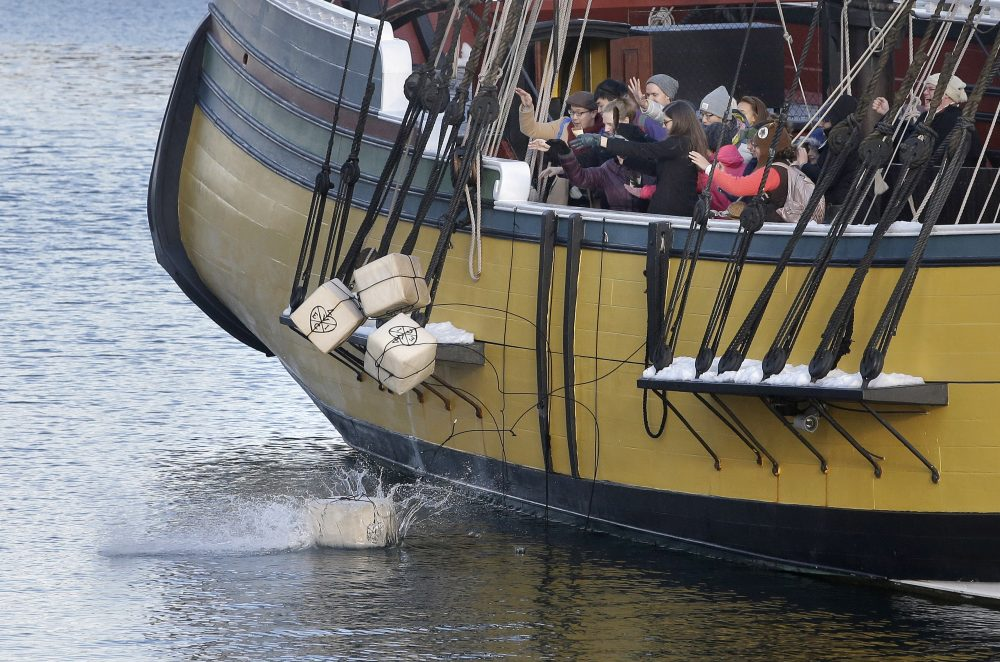 In this Monday, Dec. 11, 2017 photo, visitors to the Boston Tea Party Museum throw replicas of historic tea containers into Boston Harbor from aboard a replica of the vessel Beaver, in Boston. The museum is encouraging Americans to send unused tea leaves to toss into Boston Harbor as part of the Saturday, Dec. 16, 2017, annual re-enactment of the historic act of defiance that led to the Revolutionary War. (Steven Senne/AP)