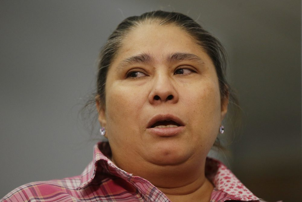 Gladys Fuentes, one of five female kitchen workers bringing a sexual harassment lawsuit against McCormick & Schmick's, recounts her experiences Tuesday in Boston. (Stephan Savoia/AP)